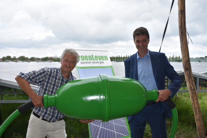 Wethouder Chris Dekker van gemeente Middelburg en Bouke Bouwman, voorzitter van Coöperatie Zonkracht Middelburg sluiten de lokale zonnebron officieel aan.